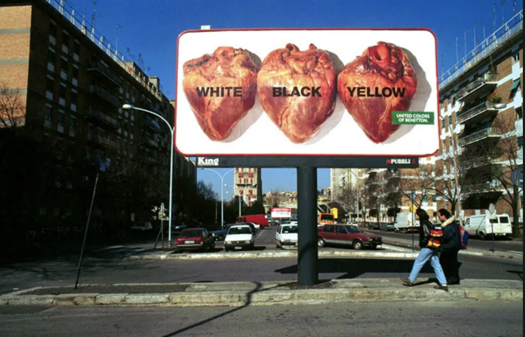 "Two people walking under a billboard in an urban setting. Image on billboard is of three organs that appear to be human hearts side by side labelled ""white"" ""black"" ""yellow"" with the green United Colors of Benetton logo."